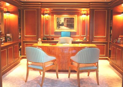 Walnut and yew wood library cabinetry and paneling with gilded accents